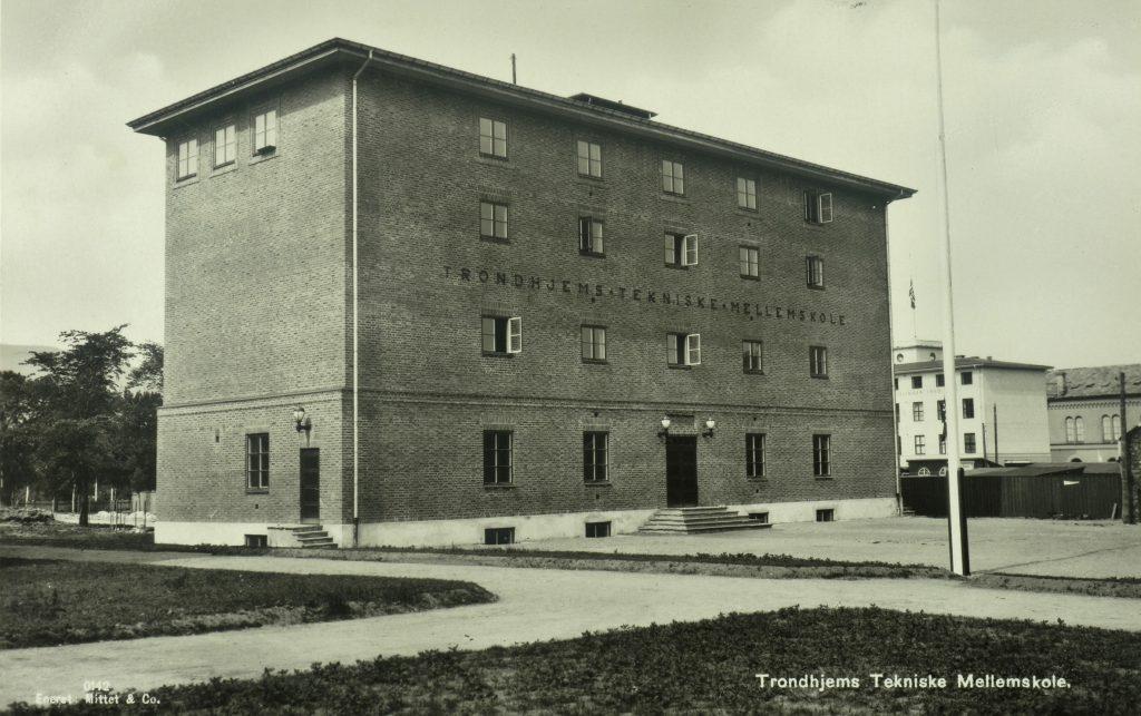 Trondhjems Tekniske Mellomskole, senere Trondheim ingeniørhøgskole, postadresse E. C. Dahls gate 2. Høgskolen i Sør - Trøndelag, her lokalene i Gunnerus gate 1. Skolen er en fortsettelse av Trondhjems Tekniske Læreanstalt (TTL), som ble opprettet 1870. Da NTH ble grunnlagt 1910 ble TTLs virksomhet fra 1912 videreført som Trondhjems tekniske mellomskole. Den hadde tilhold i nåværende Rådhuset i Munkegata 1 til 1929, da man oppførte ny skolebygning på Gassverktomta. Ark. Claus Hjelte. Foto 1929. Foto: Ukjent/NTNU UB Lisens: CC BY-SA 4.0 ID: UBT-TO-081769_01